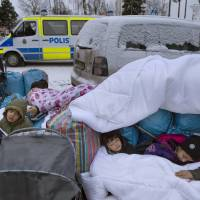 Migrant children Nor, Saleh and Hajaj Fatema from Syria sleep outside the Swedish Migration Board, in Marsta, Sweden, on Jan. 6. Interior Minister Anders Ygeman says Sweden could deport between 60,000 and 80,000 asylum seekers in coming years. Ygeman told newspaper Dagens Industri that since about 45 percent of asylum applications are currently rejected, the country must get ready to send back tens of thousands of the 163,000 who sought shelter in Sweden last year, it was reported on Thursday. | JESSICA GOW / TT NEWS AGENCY VIA AP, FILE