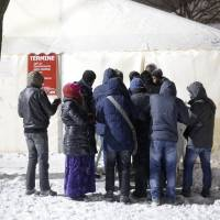 Migrants line up for an appointment in front of a waiting tent on a cold and snowy early morning, at the central registration center for refugees and asylum seekers LaGeSo (Landesamt fuer Gesundheit und Soziales — State Office for Health and Social Affairs) in Berlin, Wednesday. | AP