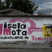 A woman walks by an electoral campaign mural of Gisela Mota, the mayor who was gunned down a day after taking office, in Temixco, Morelos State, Mexico, onMonday. The Mexican drug cartel known as Los Rojos is suspected of being behind the murder of Mota, authorities said Monday. | AFP-JIJI