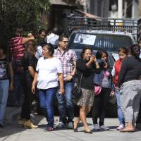 Residents react next to a crime scene where newly installed Mayor Gisela Mota was attacked at her home by four armed gunmen in Temixco, south of Mexico City, Saturday. | REUTERS