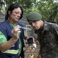 A health agent from Sao Paulo's Public health secretary shows an army soldier an Aedes aegypti mosquito larvae that she found during a cleanup operation against the insect, which is a vector for transmitting the Zika virus, in Sao Paulo Wednesday. A U.S. warning urging pregnant women to avoid travel to Latin American countries where the mosquito-borne virus is multiplying threatens to depress tourism to the region, one of its few bright spots at a time of deep economic pain. | AP