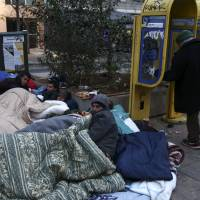 Migrants try to keep warm with blankets during their temporary stay at central Victoria square in Athens, on Friday. More than a million people reached Europe in 2015 in the continent's largest refugee influx since the end of World War II. Nearly 3,800 people are estimated to have drowned in the Mediterranean last year, making the journey to Greece or Italy in un-seaworthy vessels packed far beyond capacity. | AP