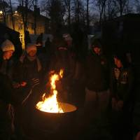 Migrants gather around a fire to warm themselves at the railway station in the southern Serbian town of Presevo Dec. 23. | AP