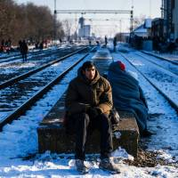 A man sits on a platform while waiting with other migrants and refugees at a train station in Presevo, Serbia, Wednesday. As refugees continued to flow from Greece through the Balkans on their way to Western Europe, aid workers sounded alarms over inadequate shelter from the current freezing temperatures and snowy conditions, particularly for children. | AFP-JIJI