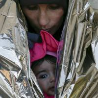 A migrant, wrapped with her child in a thermal blanket, waits for a train to Croatia, at a train station in Presevo, Serbia, Wednesday. | REUTERS