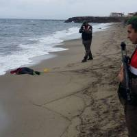 Turkish solders take photos of the body of a migrant washed up ashore in Izmir's Dikili district on Tuesday. The bodies of 17 migrants were found washed up on Turkey's western coast after boats taking them across the Aegean Sea toward EU member Greece sank in bad weather, the Dogan news agency reported. | TAYLAN YILDIRIM/ DOGAN NEWS AGENCY / AFP-JIJI