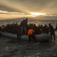 Refugees and migrants disembark on a beach after crossing a part of the Aegean sea from the Turkey's coast to the northeastern Greek island of Lesbos, on Sunday. | AP