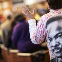 Gail Hollin wears a shirt bearing the image of the Rev. Martin Luther King Jr. as she sings during the King holiday commemorative service at Ebenezer Baptist Church where he preached, Monday in Atlanta. | AP
