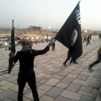 A fighter of the Islamic State of Iraq and the Levant (ISIL) holds an ISIL flag and a weapon on a street in the city of Mosul, Iraq, in June 2014. | REUTERS