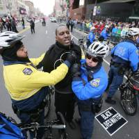 Police officers arrest protester Asa Khalif during the Mummers Day Parade on New Year's Day in Philadelphia on Friday. Dozens of activists from the Black Lives Matter movement used the parade to stage a protest. | DAVID SWANSON / THE PHILADELPHIA INQUIRER VIA AP