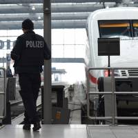 Police officers patrol in front of a train at the main train station in Munich on Friday during an alert about a potential terrorist attack in the German city.   AFP-JIJI
