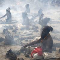 Hindu holy men perform a ritual by burning dried cow dung cakes in earthen pots at Sangam, the confluence of the Ganges, Yamuna and mythical Saraswati rivers, at the annual Magh Mela fair in Allahabad, India, on Jan. 24 last year. | AP