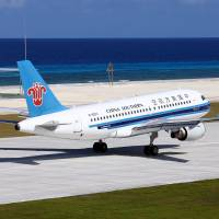 A China Southern Airline passenger plane lands at a newly built airport during a test flight to Fiery Cross Reef in the South China Sea on Wednesday. | XINHUA NEWS AGENCY / REUTERS