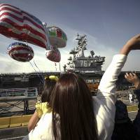 Family members of sailors wave as the U.S. Navy aircraft carrier USS Ronald Reagan arrives Oct. 1 at a U.S. Navy base in Yokosuka, Kanagawa Prefecture. The U.S. Pacific Fleet is smaller than it was in the 1990s, helping fuel a debate about whether the U.S. has enough ships to meet challenges posed by fast-growing and increasingly assertive Chinese naval forces. | AP