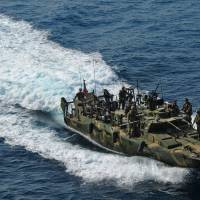 This U.S. Navy photo released Tuesday shows the type of riverine command boat apprehended by Iran on Tuesday. U.S .officials said they were working to recover 10 US Navy personnel who lost radio contact and were apprehended, in riverine command boats after straying into Iranian territorial waters. In the picture, a boat from Riverine Detachment 23 operates with the amphibious transport dock ship USS New York (LPD 21), not pictured, during a maritime air support operations center exercise on June 12, 2012 | US NAVY PHOTO BY MASS COMMUNICATION SPECIALIST 2ND CLASS ZANE ECKLUN / U.S. NAVY / AFP-JIJI