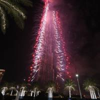 Fireworks illuminate the Burj Khalifa as a tower burns behind it, lower right of tower, in Dubai, United Arab Emirates, on Friday. | AP