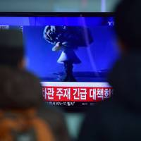 People watch a news report on North Korea's claimed first hydrogen bomb test at a railroad station in Seoul on Wednesday. The image shown on TV is a file picture from nuclear tests by other countries. | AFP-JIJI