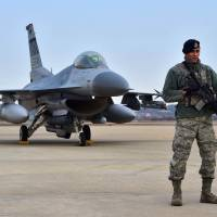 A U.S. soldier stands guard in front of an F-16 fighter jet after a press briefing on the flight by a B-52 Stratofortress over South Korea at Osan Air Base in Pyeongtaek, South Korea, on Sunday. | AFP-JIJI