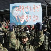 A South Korean war veteran holds up a picture of North Korean leader Kim Jong Un during a rally against Pyongyang's nuclear test, in Seoul on Saturday. The placard reads 'Anti-North Korea loudspeaker? Leaflets? Kim Jong Un is smiling!' | AP