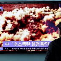 A man at a train station in Seoul on Jan. 6 watches a news broadcast discussing North Korea's nuclear test. | BLOOMBERG