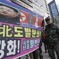 A banner shows a picture of North Korean leader Kim Jong Un as South Korean war veterans stage a rally against Pyongyang in Seoul on Saturday. The banner's text reads 'Smash the North Korean provocation which threatens peace in the global village!' | AP