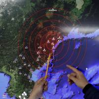 A Korea Meteorological Administration official points at where seismic tremors are thought to have originated following an apparent nuclear test in North Korea. The official was taking part in a news briefing in Seoul on Jan. 6. | REUTERS