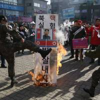 A member of a South Korean conservative group kicks a burning banner bearing the image of North Korean leader Kim Jong Un and the country's flag during a rally denouncing Pyongyang in Paju, South Korea, on Monday. | AP
