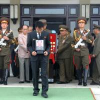 A man carries a portrait of Jon Pyong Ho during his state funeral in this undated photo released by North Korea's Korean Central News Agency (KCNA) in Pyongyang on July 10, 2014. | KCNA / REUTERS