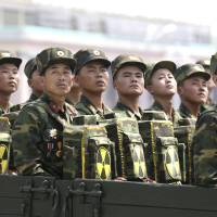 North Korean soldiers turn and look toward leader Kim Jong Un in 2013 as they carry packs marked with the nuclear symbol during a parade marking the 60th anniversary of the Korean War armistice in Pyongyang. It's a single image released by an enormous propaganda apparatus, showing a note handwritten by a dictator. And it contains a telling clue to the mindset behind what has become the biggest story in Asia: North Korea's surprise and disputed claim to have tested its first hydrogen bomb. | AP