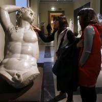 South Koreans admire a marble statue of Dionysus at the Capitoline Museums in Rome on Tuesday. | AP