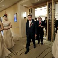 Wang Jianlin (center front), chairman of Dalian Wanda Group, and Atletico Madrid's President Enrique Cerezo arrive for a signing ceremony in Beijing on Jan. 21, 2015, when Wanda bought a 20 percent stake in the Spanish soccer club. | REUTERS
