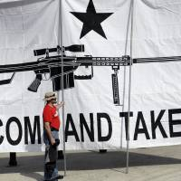 A demonstrator stabilizes a giant banner at a rally in support of open-carry gun laws in Austin, Texas. President Obama has pledged to action on the availability of firearms during his final year in office. | AP