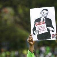 A protestor holds up an anti-TPPA (Trans-Pacific Partnership Agreement) placard with U.S. President Barack Obama's caricature during a protest in Kuala Lumpur Saturday. | AP