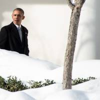 U.S. President Barack Obama walks through the colonnade at the White House in Washington on Monday on his way to visit wounded service members at the Walter Reed National Military Medical Center in Bethesda, Maryland. | AFP-JIJI