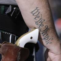 Scott Smith, a supporter of open carry gun laws, wears a pistol last Jan. 26 as he prepares for a rally in support of open carry gun laws at the Capitol, in Austin, Texas. Texas the second-most populous state, is joining 44 other states in allowing at least some firearm owners to carry handguns openly in public places. | AP