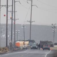 A vehicle is stopped at a checkpoint along Highway 78 located approximately 4 miles from the Malheur Wildlife Refuge Headquarters near Burns, Oregon, on Thursday. A convoy of armored vehicles rolled into the wildlife refuge in Oregon where a handful of armed protesters are holed up in a drawn-out standoff with the federal government that turned deadly this week. | AFP-JIJI