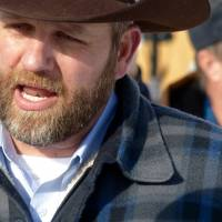 Ammon Bundy chats with a protester Saturday during a march on behalf of a Harney County ranching family in Burns, Oregon. Bundy, the son of Nevada rancher Cliven Bundy, who was involved in a standoff with the government over grazing rights, told The Oregonian that he and two of his brothers were among a group of dozens of people occupying the headquarters of the Malheur National Wildlife Refuge. | LES ZAITZ / THE OREGONIAN VIA AP