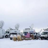 Media and satellite trucks are seen at the Malheur National Wildlife Refuge near Burns, Oregon, Monday. | REUTERS
