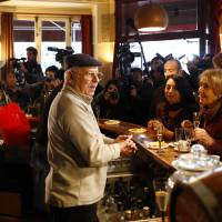 Owner of the Carillon restaurant, Mokrane Hadjem, nicknamed 'Coco,' welcomes customers during the reopening exactly two months after the November attacks, in Paris, Wednesday. With the blood and bullets now swept away, the Carillon cafe has reopened its doors for the first time since it was among the Paris sites targeted by Islamic extremists. | AP