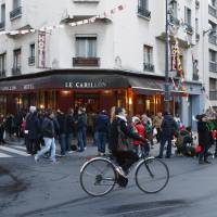 Customers drink on the terrace of the Carillon cafe during the reopening exactly two months after the November attacks in Paris Wednesday. | AP