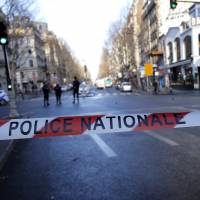 Police officers cordon off the area of a fatal shooting which took place at a police station in Paris on Thursday. | AP