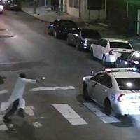 Edward Archer runs with a gun toward a police car driven by officer Jesse Hartnett in Philadelphia on Thursday in this image from surveillance video. | AP