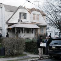 An investigator takes a box from one of the residences where suspect Edward Archer has lived Friday in Yeadon, Pennsylvania. Archer, accused of ambushing a police officer and firing shots at point-blank range, said he was acting in the name of Islam and had pledged allegiance to the Islamic State group, Philadelphia authorities said Friday. | AP