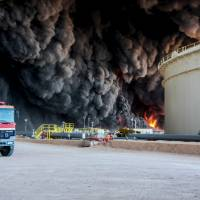 Fire rises from an oil tank in the port of Es Sider, in Ras Lanuf, Libya, Jan. 6. A blast ripped through a pipeline at a nearby complex Thursday and sabotage is suspected. | REUTERS