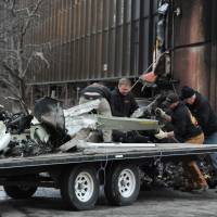 Workers load the remains of a small plane that crashed into two office buildings in downtown Anchorage, Alaska, Tuesday. | BOB HALLINEN / ALASKA DISPATCH NEWS VIA AP