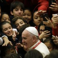 Pope Francis leaves at the end of an audience he held for the Pueri Cantores (children's choirs), at the Pope Paul VI hall at the Vatican, Thursday. | AP