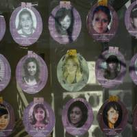 Photos of missing women are pasted in a window inside a memorial park erected on the spot where eight women were found murdered and dumped in a cotton field in 2001 in Ciudad Juarez, Mexico, Sunday. | AP