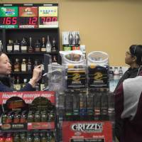 Ali Tsedev sells Powerball lottery tickets at a convenience store in Washington, D.C., Thursday. Lottery officials predict Saturday's jackpot will reach $700 million, the largest in history. | AFP-JIJI