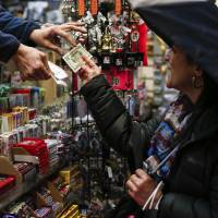 A woman buys from a newsstand a Powerball lottery ticket in New York City on Tuesday. Record sales drove up the largest jackpot in US history to a whopping $1.5 billion as people dreaming of riches flocked across state lines and international borders to buy tickets. | AFP-JIJI