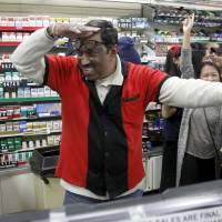 7-Eleven clerk M. Faroqui celebrates Wednesday after selling a winning Powerball ticket in Chino Hills, California.  | REUTERS
